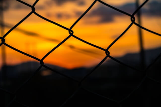 photo of sunset with chain link fence