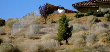 desert house surrounded by a chain link fence