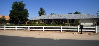house with ranch style white vinyl fencing