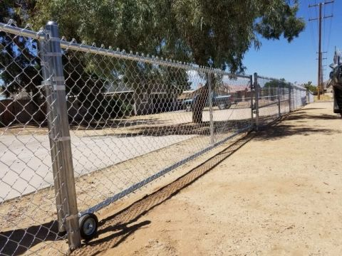 chain link fence on top of sandy ground
