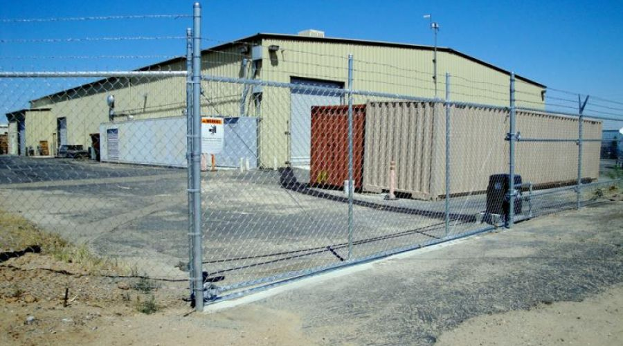 A large warehouse behind a security chain link fence